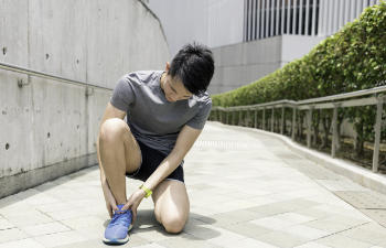 man squats holding on to the ankle, ankle pain, runner