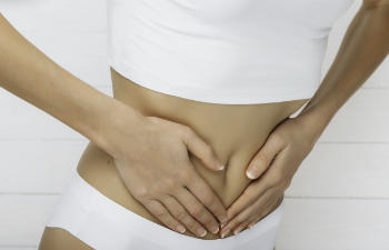 Young athletic woman in white underwear keeps her hands on her stomach.
