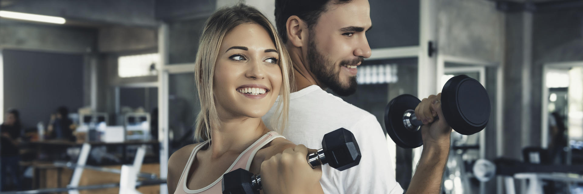 couple at the gym exercising with weights, happy, healthy, young people