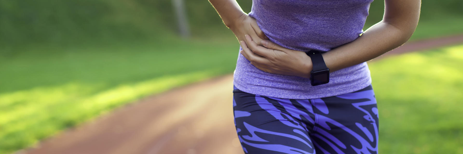 An athletic woman with pain in the side of stomach caused by hernia.